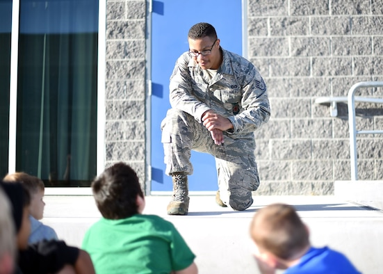 A uniformed member of the Air Force bends down on on knee to speak with grade-school aged children. It's sunny. The children listen to the Airman attentively.