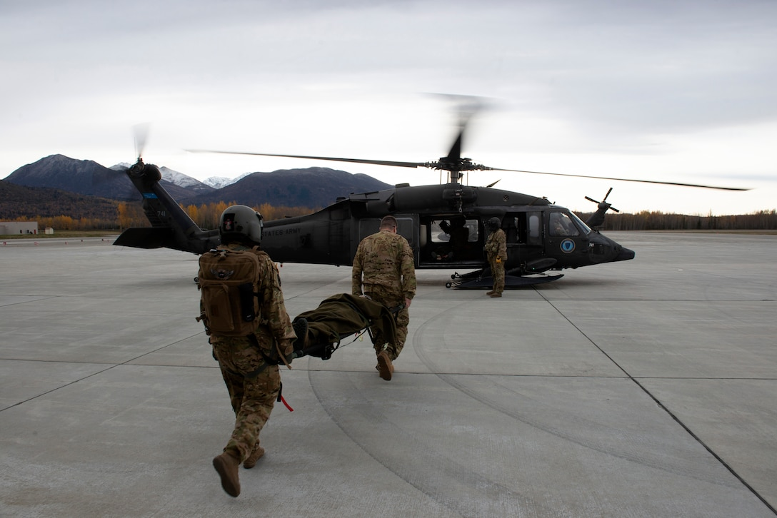 U.S. Army Staff Sgt. Mikana Halloran, flight medic, and U.S. Army Maj. Titus Rund, flight surgeon, both with the 2-104th G. Company, 2nd Battalion, 2nd Detachment, Air Ambulance, Alaska Army National Guard, load an Airman with a simulated injury into an AKARNG UH-60L Black Hawk for a medical evacuation during Polar Force 20-1 at Joint Base Elmendorf-Richardson, Alaska, Oct. 8, 2019. Designed to test JBER's mission readiness, Polar Force 20-1 is a two-week exercise that hones Airmen's skills and experience when facing adverse situations. Airmen refined their contingency tactics, techniques and procedures in support of the Pacific Air Force's Agile Combat Employment concept of operations. Agile Combat Support excellence yields multi-domain operations success.