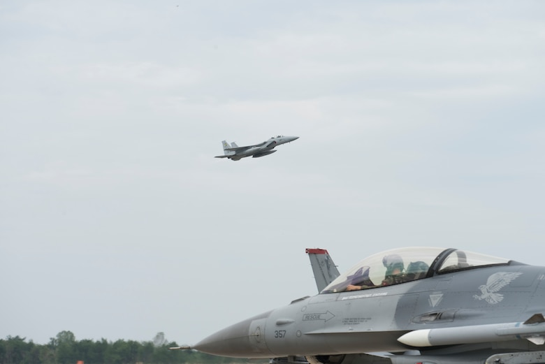 A Mitsubishi F-15J flies above a taxiing F-16 Fighting Falcon during an aviation training relocation at Komatsu Air Base, Japan, Oct. 2, 2019. The 28 stories executed during the ATR gave Wild Weasel's the ability to learn, train and integrate with their host nation partners while identifying successes and shortfalls. The F-15J is assigned to the 6th Air Wing Maintenance Squadron, Komatsu AB, and the F-16 is assigned to the 35th Maintenance Squadron from Misawa AB. (U.S. Air Force photo by Senior Airman Collette Brooks)