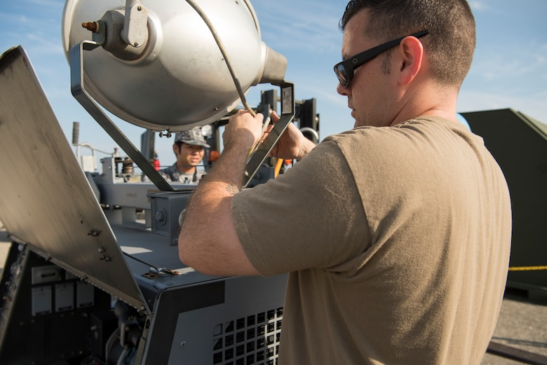 U.S. Air Force Tech. Sgt. Jesse Reddam, the 35th Maintenance Squadron aerospace ground equipment inspection and repair section chief, sets up AGE equipment during an aviation training relocation at Komatsu Air Base, Japan, Oct. 1, 2019. The week-long exercise included within visual range air-to-air combat, bilateral aircraft recovery, refueling, launching and joint usage and training of AGE equipment. (U.S. Air Force photo by Senior Airman Collette Brooks)