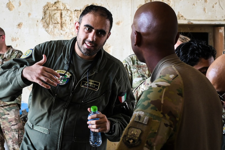 U.S. Air Force service members give a tour of their work area to Kuwaiti air force members at Ahmed Al Jaber Air Base, Kuwait, Sept. 25, 2019. Both militaries participated in a subject matter expert exchange on cargo transportation and preparation, learning about each other's processes and providing feedback. (U.S. Air Force photo by Senior Airman Lane T. Plummer)