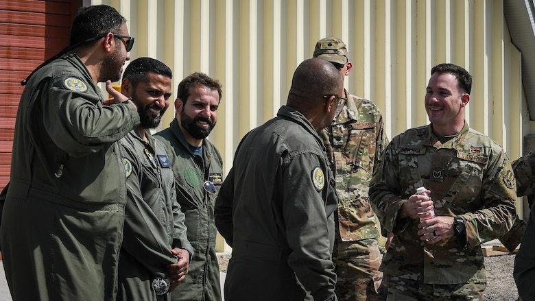 U.S. Air Force service members laugh with their Kuwaiti air force counterparts while they tour U.S. units at Ali Al Salem Air Base, Kuwait, Sept. 24, 2019. Both militaries participated in a subject matter expert exchange on cargo transportation and preparation, learning about each other's processes and providing feedback. (U.S. Air Force photo by Senior Airman Lane T. Plummer)
