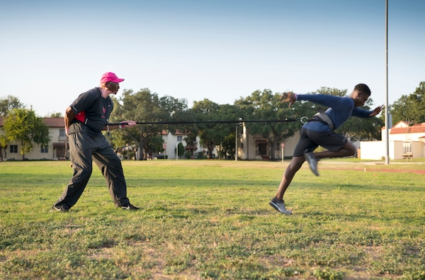 Tony Lightner holds a resistant band while training JaCorey Anderson during track and field practice Oct. 2 at JBSA Randolph. Lightner, despite health hurdles, has trained kids in track and field for free since 2006.