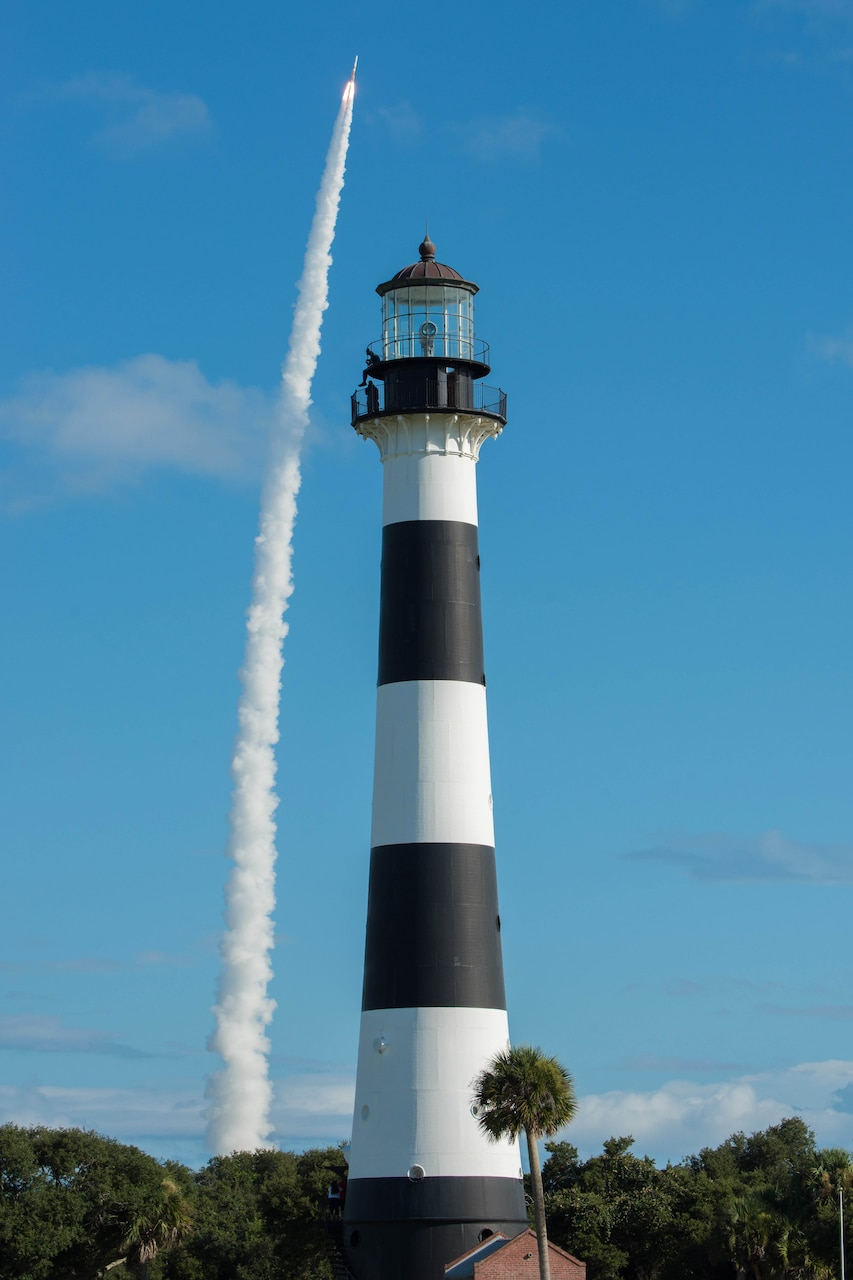 A rocket launches into the sky behind a tall black and white lighthouse.