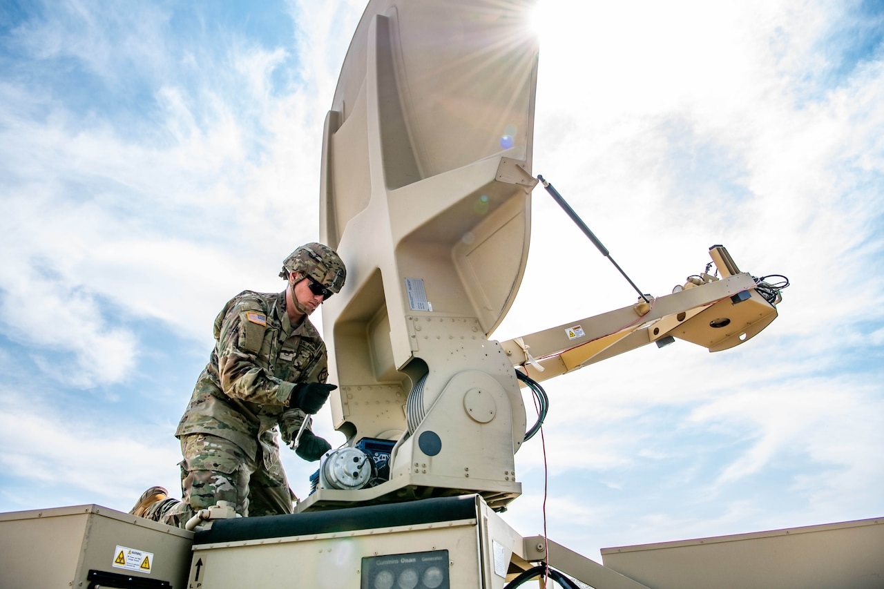 Soldier sets up satellite dish.