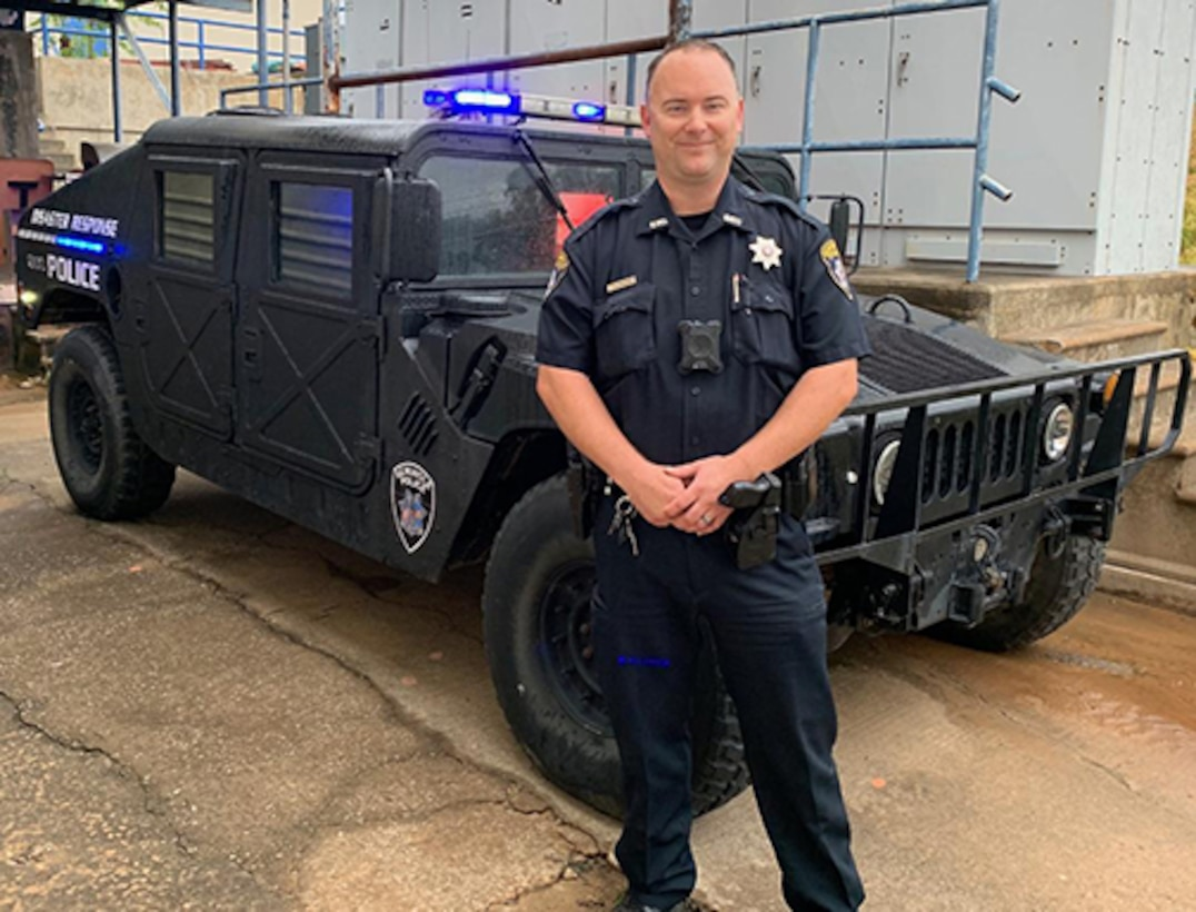 Police officer stands in front of Humvee.