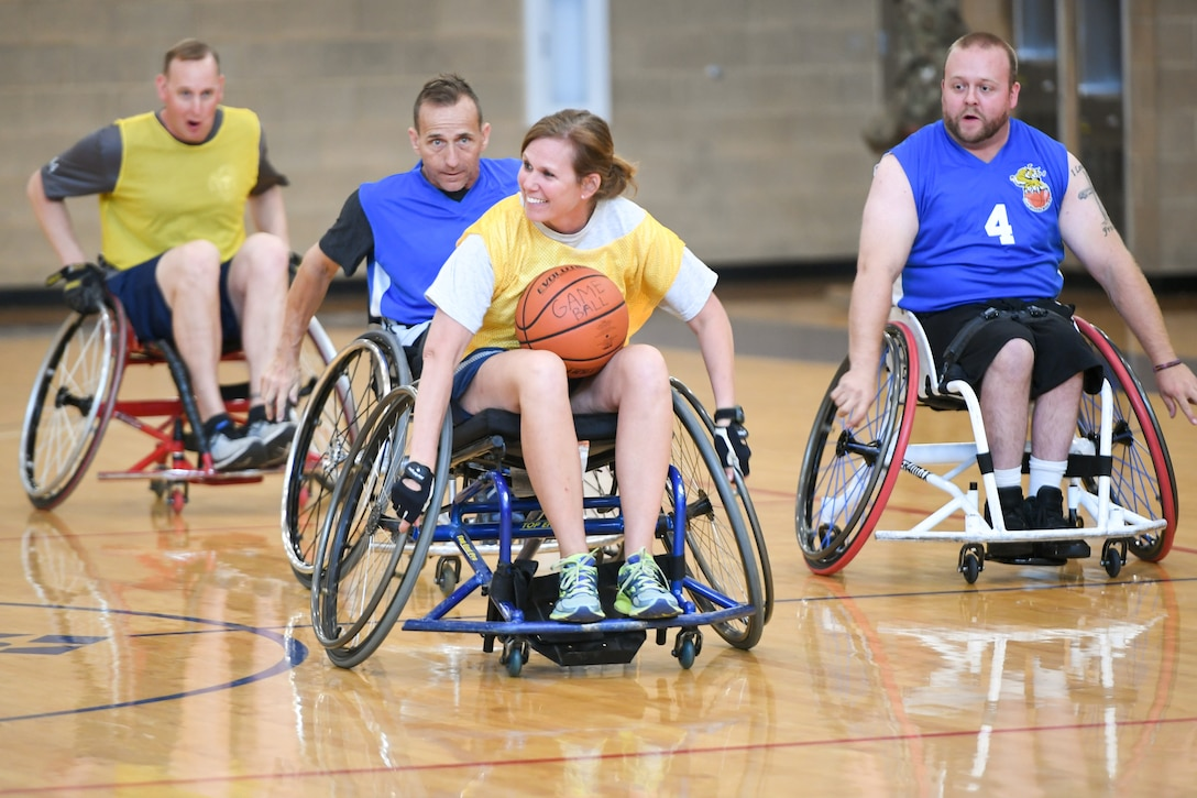 Colonel Regina Sabric, 419th Fighter Wing commander, runs with the ball during a wheelchair basketball game Oct. 9, 2019 at Hill Air Force Base, Utah. Leaders from Hill's units faced off against the Ogden Wheelin' Wildcats, a semi-professional wheelchair basketball team, to celebrate National Disability Employment Awareness Month. (U.S. Air Force photo by Cynthia Griggs)