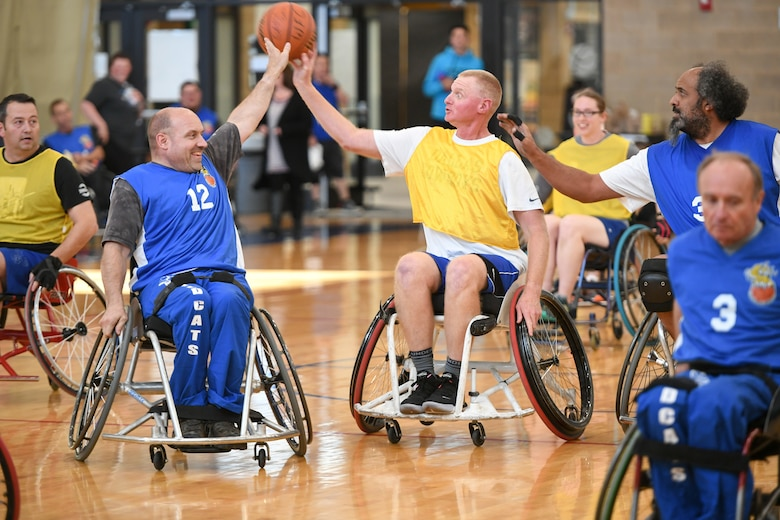 Colonel Jon Eberlan, 75th Air Base Wing commander, spars for ball possession with a player from the Ogden Wheelin' Wildcats during a wheelchair basketball game Oct. 9, 2019 at Hill Air Force Base, Utah. Leaders from Hill's units faced off against the Wheelin' Wildcats, a semi-professional wheelchair basketball team, to celebrate National Disability Employment Awareness Month. (U.S. Air Force photo by Cynthia Griggs)