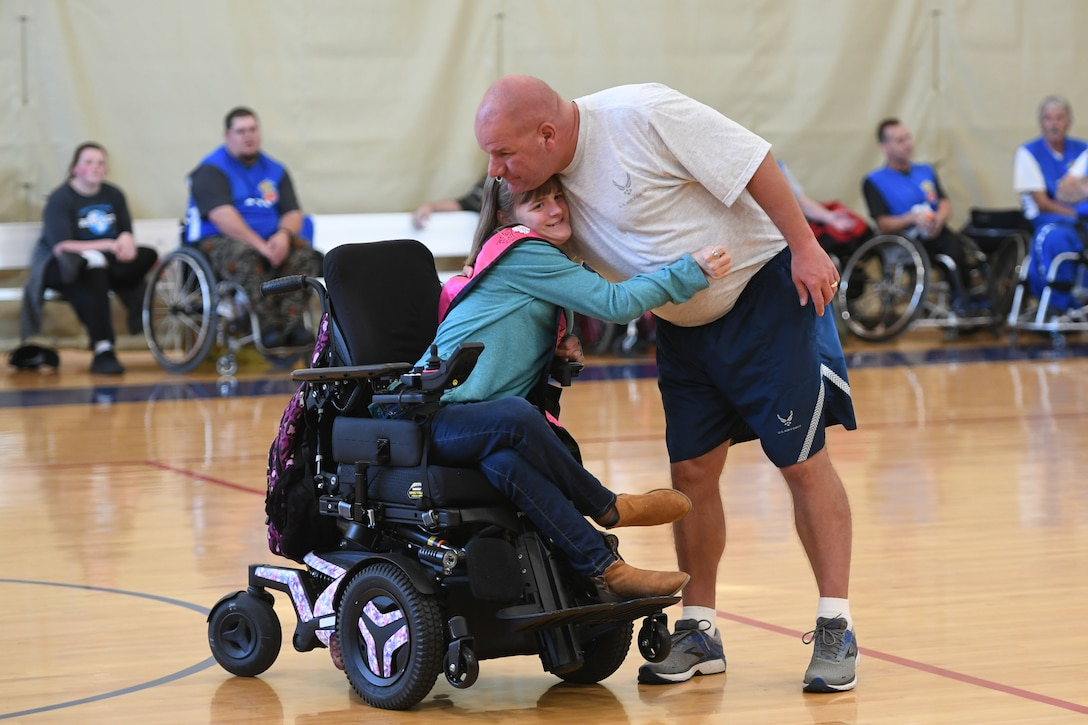 Master Sgt. Scott Heim, 388th Maintenance Squadron, hugs his daughter Brianna during halftime while being introduced as one of the basketball players who has an exceptional family member. Leaders from Hill's units faced off against the Ogden Wheelin' Wildcats, a semi-professional wheelchair basketball team, to celebrate National Disability Employment Awareness Month. (U.S. Air Force photo by Cynthia Griggs)