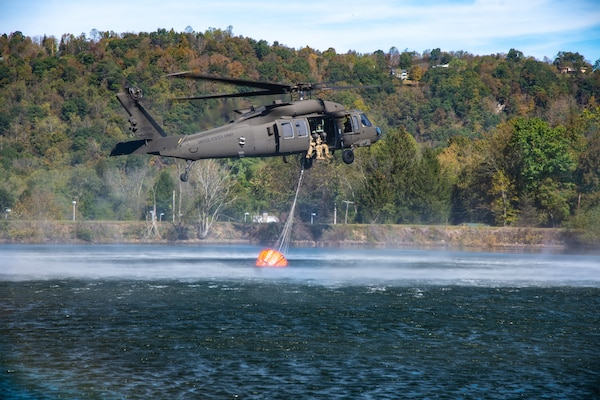 Members of West Virginia Army National Guard Company C, 1st Battalion, 150th Aviation Regiment, practice using a helicopter bucket to fight fires at Camp Dawson, West Virginia, Oct. 10, 2019. The training prepares aircrew members to respond with civilian firefighting agencies to wildfires.