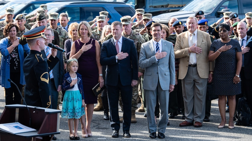 Defense Secretary Dr. Mark T. Esper and other people hold their hands over the hearts.
