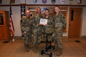 U.S. Air Force Col. Zachery Jiron, center left, 60th Air Mobility Wing vice commander, Chief Master Sgt. Matt Pulsipher, left, 60th Comptroller Squadron and Wing Staff Agency superintendent, and Master Sgt. Randel Moser, right, 660th Aircraft Maintenance Squadron aircraft section chief, recognize Staff Sgt. Mark Hedge, center right, 660th Aircraft Maintenance Squadron Aerospace Propulsion craftsman, as Warrior of the Week Oct. 8, 2019, at Travis Air Force Base, California. Hedge was recognized as the 60th Air Mobility Wing Warrior of the Week for Oct. 6-12, 2019. The program highlights a Travis Airman or noncommissioned officer for his or her outstanding performance. (U.S. Air Force photo by Airman 1st Class Cameron Otte)