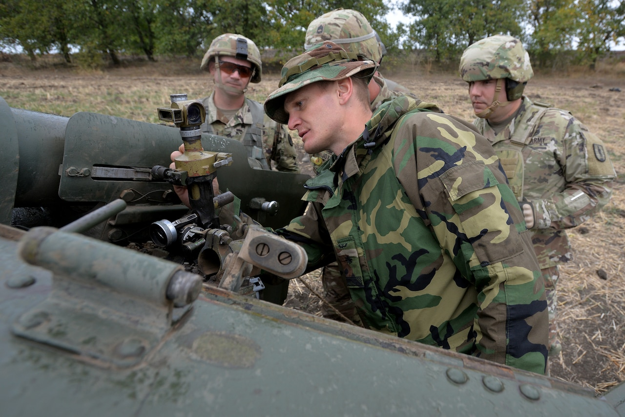 One soldier examines an artillery piece as three others look on.