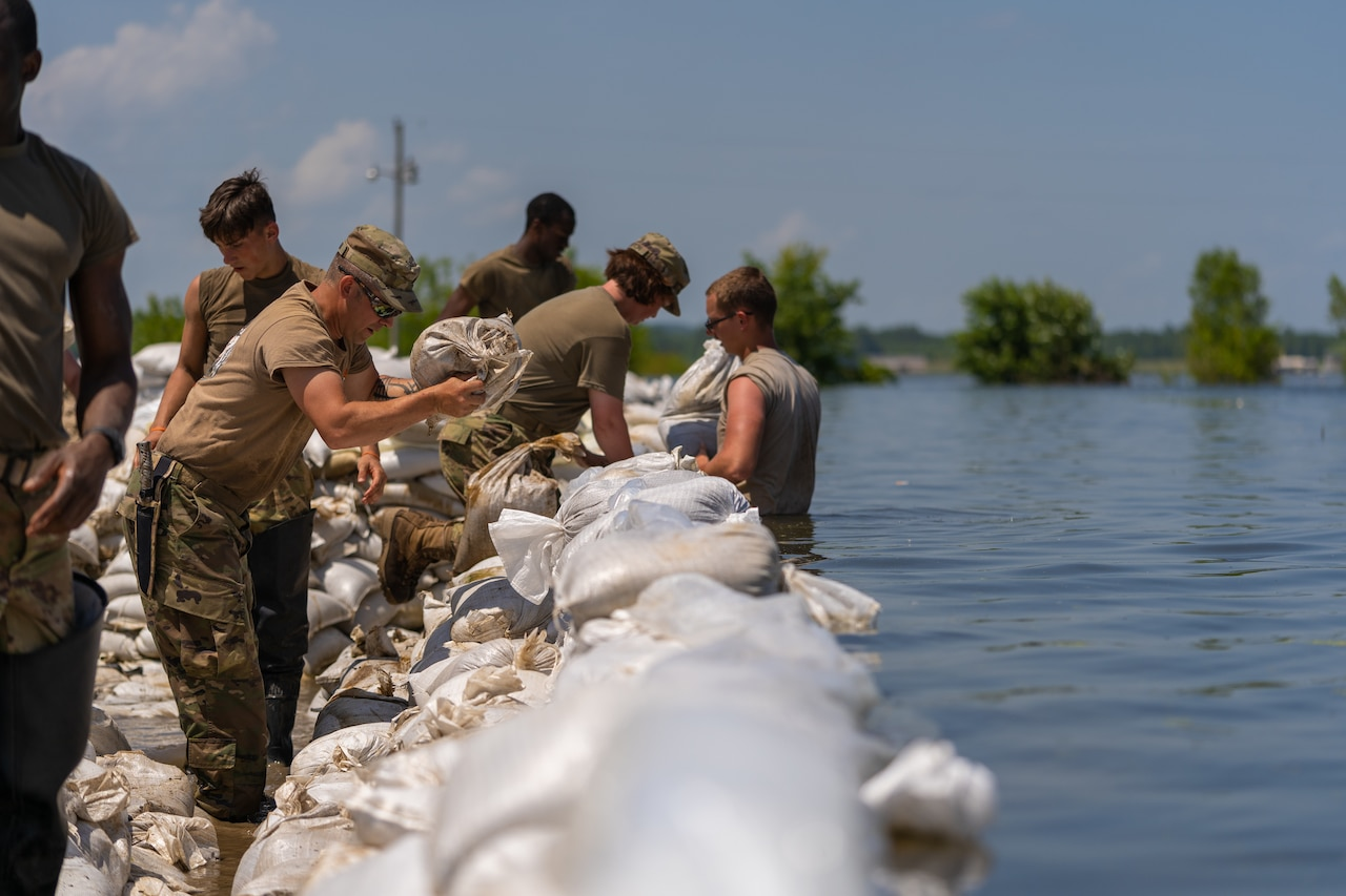 A guardsman standing in waist-high water works with other service members to place sandbags on a levee.