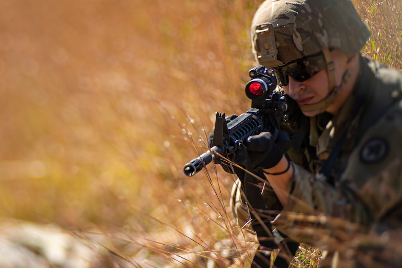 A soldier crouched in field of tall grass aims a weapon.
