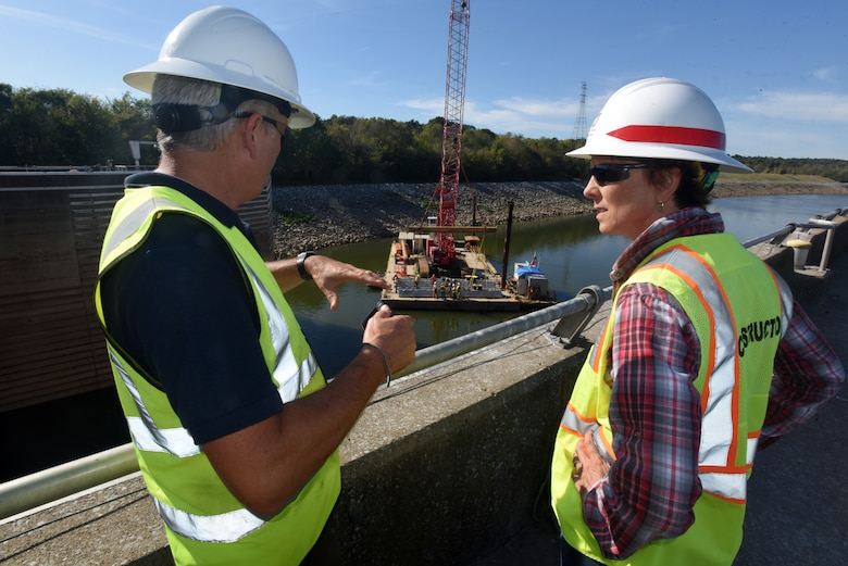 David Lambert, project manager with Fish Guidance Systems, and Jill Kelley, project manager with the U.S. Army Corps of Engineers Nashville District, watch as a crew prepares to install a section of the bio acoustic fish fence Oct. 9, 2019 on the riverbed below Barkley Lock in Grand Rivers, Ky. (USACE photo by Lee Roberts)