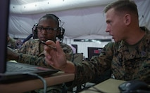 Gunnery Sgt. Zachary S. Crone, right, speaks with Marine Cpl. Trevor W. Allen during Exercise Pegasus Flight at Marine Corps Air Station Cherry Point, North Carolina, Sept. 30, 2019. Marine Tactical Air Command Squadron 28 supported Pegasus Flight by planning, commanding, directing and supervising all air operations as the tactical air command center for the exercise. Crone is a tactical air defense controller and Allen is a air support operations operator with MTACS-28, Marine Air Control Group 28, 2nd Marine Aircraft Wing. (U.S. Marine Corps photo by Pfc. Steven M. Walls)