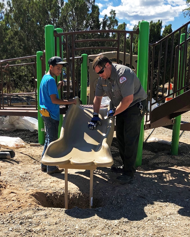 Abiquiu Lake project office manager John Mueller, right, works with a volunteer on the installation of an ADA-accessible playground at the lake on National Public Lands Day, Sept. 28, 2019.