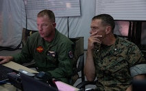 Marine Lt. Col. James P. Doyle, left, informs Lt. Col. Kristopher L. Faught on the status of a simulation during Exercise Pegasus Flight at Marine Corps Air Station Cherry Point, North Carolina, Oct. 1, 2019. Pegasus Flight was organized to support unit-level training objectives in a limited capability environment to improve combat readiness and mission effectiveness against near-peer threats. Doyle is a weapons systems officer with Marine Wing Headquarters Squadron 2 and Faught is an operations officer with MWHS-2, 2nd Marine Aircraft Wing. (U.S. Marine Corps photo by Pfc. Steven M. Walls)