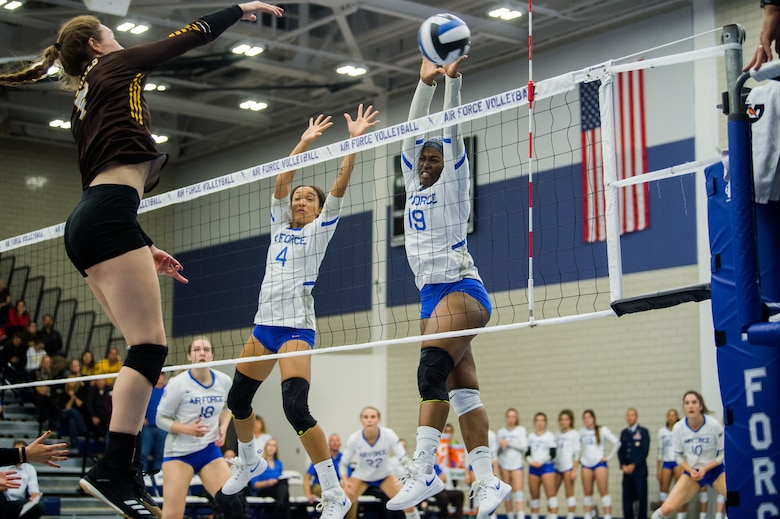 USAF cadets jump to block a spike during a volleyball match