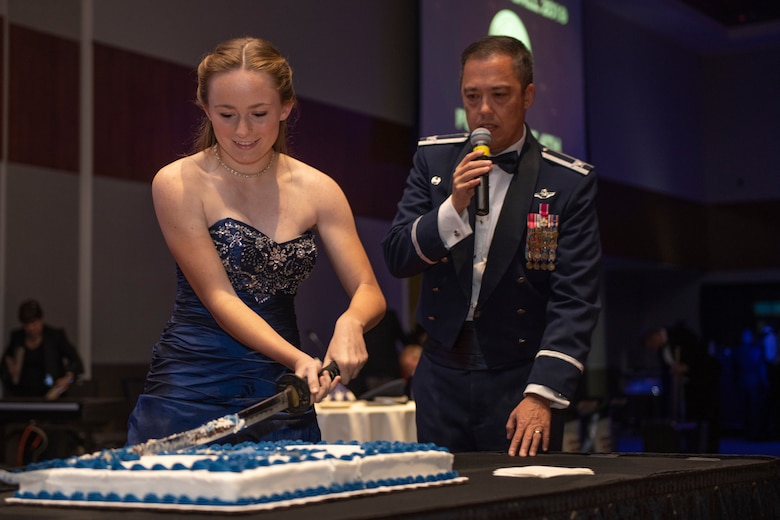 Airman cuts the first slice of cake during the Air Force Ball