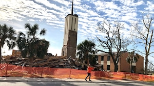 A construction worker carries a cross after an excavator demolished the Tyndall Air Force Base, Florida, chapel in February. The Tyndall Chapel was unable to be restored after sustaining immense damage from Hurricane Michael on Oct. 10, 2018. (U.S. Air Force photo)