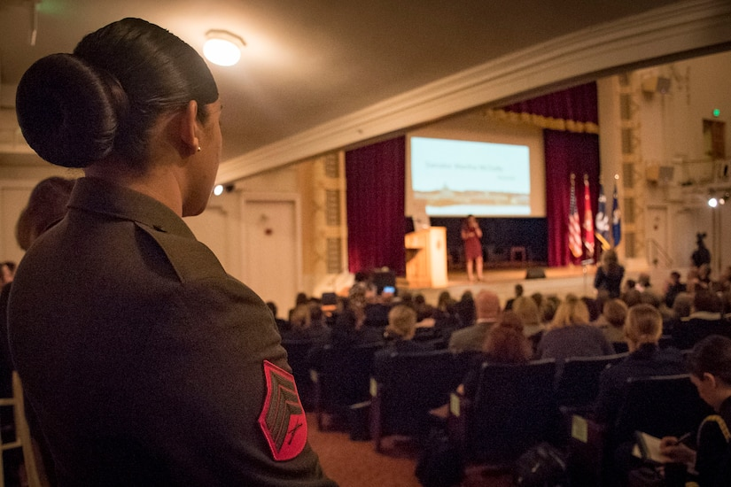 A Marine stands near the rear of an auditorium as a speaker addresses an audience.