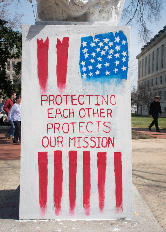 "A red, white and blue painting of a stylized vertical U.S. flag superimposed by text reading, ""protecting each other protects our mission."""