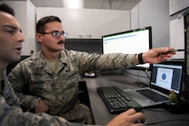 Airman 1st Class Aws Hussein, 66th Comptroller Squadron financial management technician, points to a computer screen while reviewing operating procedures with Staff Sgt. Josh Pimentel, 66 CPTS financial management supervisor, on Hanscom Air Force Base, Massachusetts, Oct. 10. Hussein served as an interpreter for U.S. troops in Iraq before immigrating to the U.S. in 2013.