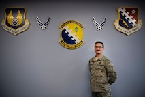 Airman 1st Class Aws Hussein, 66th Comptroller Squadron financial management technician, stands under the Air Force Material Command, 66th Air Base Group and CPTS crests on Hanscom Air Force Base, Massachusetts, Oct. 10. Originally from Baghdad, Iraq, Hussein worked alongside coalition forces as an Arabic interpreter from 2007 to 2011. He immigrated to the U.S. with his wife and two young children before enlisting in the Air Force earlier this year.