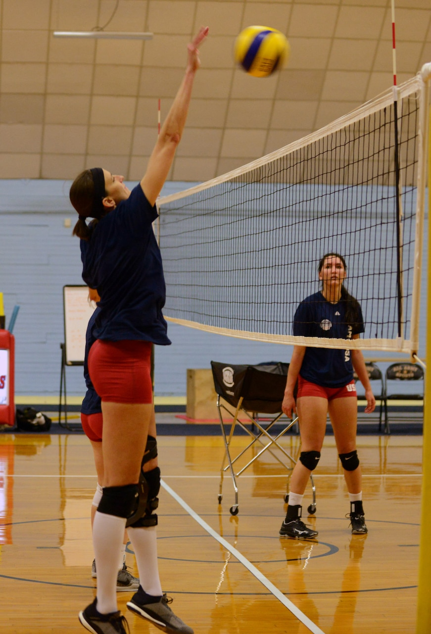 Woman jumps with both arms extended over her head to hit a volleyball.