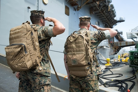 U.S. Marine Corps Lance Cpl. Jose Elias, left, and U.S. Navy Petty Officer 3rd Class Justin Chandler, right, both currently assigned to Special Purpose Marine Air Ground Task Force – WASP, render salutes before boarding the USS Wasp (LHD 1) on Naval Base San Diego, Sept. 22, 2019.