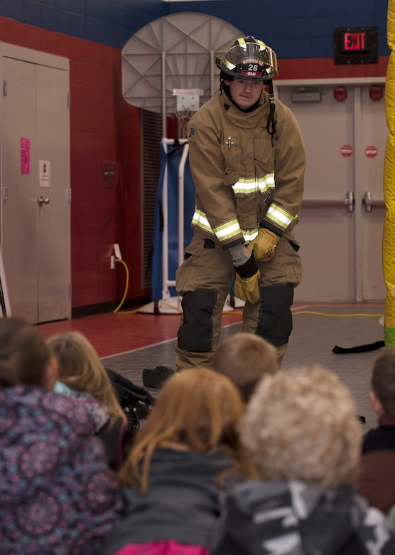 "Airman 1st Class Jacob Adamson, assigned to the Fire and  Emergency Services Team at Whiteman Air Force Base, Missouri, demonstrates how he can don his uniform in 60 seconds to a first grade class to Whiteman Elementary on October 10, 2019. The 2019 Fire Prevention Week campaign theme is ""Not Every Hero Wears a Cape. Plan and Practice Your Escape"". (U.S. Air Force photo by Staff Sgt. Kayla White)"