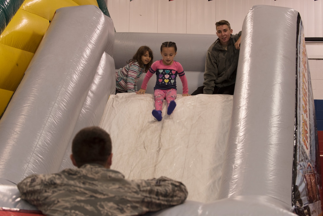 "Airman Andrew Tassey, a member of the Fire and Emergency Services Team at Whiteman Air Force Base, Missouri, supervises Whiteman Elementary first graders as they slide down a bouncy house slide on October 10, 2019. The 2019 Fire Prevention Week campaign theme is ""Not Every Hero Wears a Cape. Plan and Practice Your Escape"". (U.S. Air Force photo by Staff Sgt. Kayla White)"