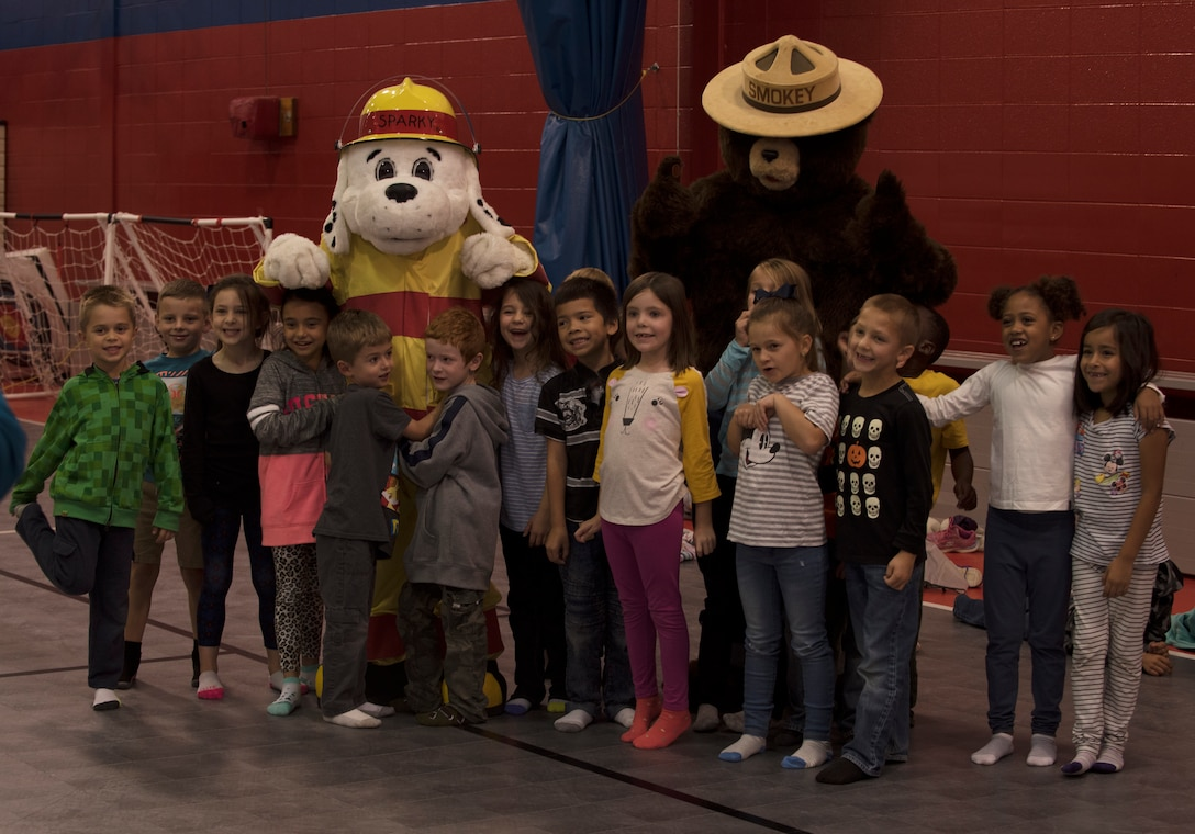 """Sparky the Dog and Smokey the Bear, mascots for the Fire and Emergency Services Team at Whiteman Air Force Base, Missouri, pose for a photo with first graders from Whiteman Elementary on October 10, 2019. The 2019 Fire Prevention Week campaign theme is """"Not Every Hero Wears a Cape. Plan and Practice Your Escape"""". (U.S. Air Force photo by Staff Sgt. Kayla White)"""