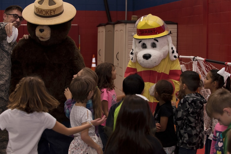 "Sparky the Dog and Smokey the Bear, mascots for the Fire and Emergency Services Team at Whiteman Air Force Base, Missouri, talk to first graders from Whiteman Elementary on October 10, 2019. The 2019 Fire Prevention Week campaign theme is ""Not Every Hero Wears a Cape. Plan and Practice Your Escape"". (U.S. Air Force photo by Staff Sgt. Kayla White)"
