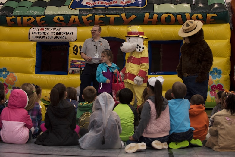 "Andrew wells, a fire inspector assigned to the Fire and Emergency Services Team at Whiteman Air Force Base, Missouri, presents a prize bag to Madison Sprouls, a first grader from Whiteman Elementary on October 10, 2019, at the Youth Center. The 2019 Fire Prevention Week campaign theme is ""Not Every Hero Wears a Cape. Plan and Practice Your Escape"". (U.S. Air Force photo by Staff Sgt. Kayla White)"