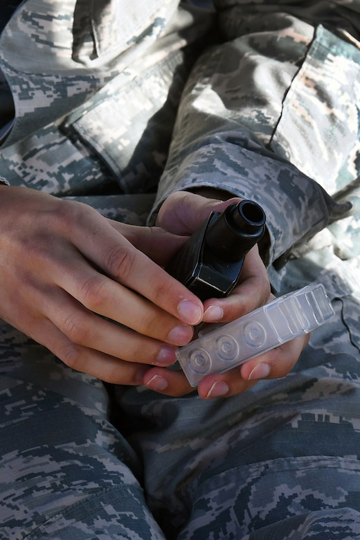 A service member holds a vape device near his lap.