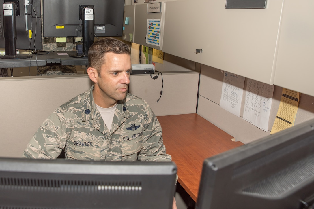 Lt. Col. Bob Brawley, the Individual Mobilization Augmentee (IMA), to the Division Chief, Plans, Programs and Readiness at Headquarters Readiness and Integration Organization (HQ RIO),  prepares emergency notifications for potential typhoon Hagibis on Oct. 11, 2019, at Buckley Air Force Base, Colo. HQ RIO members such as Brawley are focused on improving inefficient processes and providing outstanding administrative support for the IMA community, making it easier for them to serve. (U. S. Air Force photo by Master Sgt. Eric Amidon)