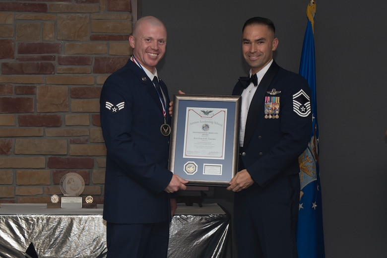 Senior Airman Travis Coursey, Airman Leadership School graduate, accepts the distinguished graduate award during the graduation of ALS class 19-7, October 10, 2019, on Holloman Air Force Base, N.M. The distinguished graduate award is presented to the top ten-percent of graduates for their performance in academic evaluations and demonstration of leadership. (U.S. Air Force photo by Airman 1st Class Kristin Weathersby)