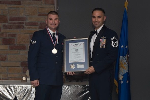 Senior Airman Chase Feeney, Airman Leadership School graduate, accepts the distinguished graduate award during the graduation of ALS class 19-7, October 10, 2019, on Holloman Air Force Base, N.M. The distinguished graduate award is presented to the top ten-percent of graduates for their performance in academic evaluations and demonstration of leadership. (U.S. Air Force photo by Airman 1st Class Kristin Weathersby)