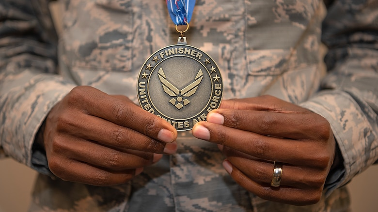 Airman 1st Class Daniel Kirwa, a medical technician assigned to the 6th Healthcare Operations Squadron, pauses for a photo with his finisher medal from the Air Force Marathon, Oct. 9, 2019. Kirwa placed first in the military category of the Air Force Marathon, and third overall, with a time of 2 hours, 33 minutes, and 3 seconds.