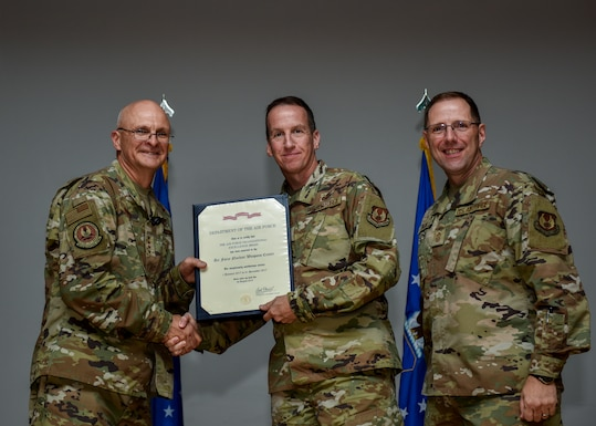 Air Force Materiel Command's commander, Gen. Arnold W. Bunch, Jr., (left), shakes hands with Maj. Gen. Shaun Q. Morris, Air Force Nuclear Weapons Center commander, as he presents him with the center's sixth Air Force Organizational Excellence award on Sept. 11, 2019, at Kirtland AFB, New Mexico. Chief Master Sgt. Stanley Cadell (right), AFMC command chief, also congratulated the center for its accomplishment. The 2018 award is for the 2017 calendar year, which marks the ninth consecutive year the center has received the award since its inception in March 2006. (U.S. Air Force photo by Airman 1st Class Austin J. Prisbrey)