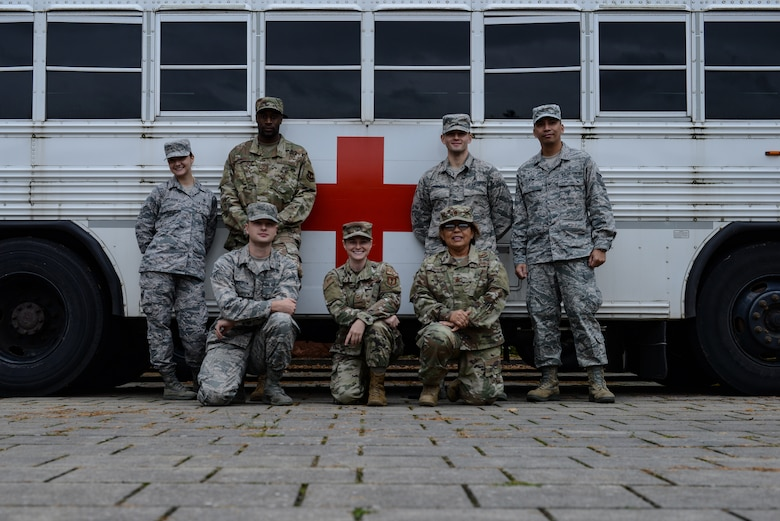 A group of U.S. Air Force service members from the 86th Aerospace Medicine Squadron pose in front of a medical transport shuttle at Ramstein Air Base, Germany, Oct. 9, 2019.