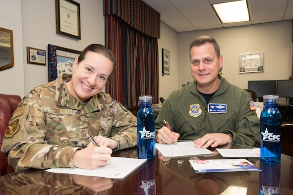 Col. Joel Safranek, right, 436th Airlift Wing commander, and Chief Master Sgt. Shae Gee, 436 AW command chief,  sign their 2019 Combined Federal Campaign pledge forms Oct. 11, 2019, at Dover Air Force Base, Del. The campaign runs from Oct. 7 through Nov. 18, 2019. Interested donors can see their unit representative or visit www.cfcgiving.opm.gov. (U.S. Air Force photo by Mauricio Campino)
