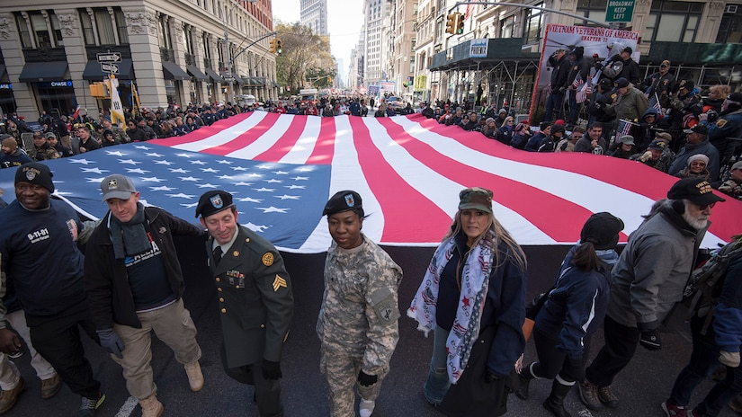 Soldiers in uniform and members of the public carry a huge American flag at shoulder-height in a parade on the streets of New York City. Vietnam veterans are in the background.