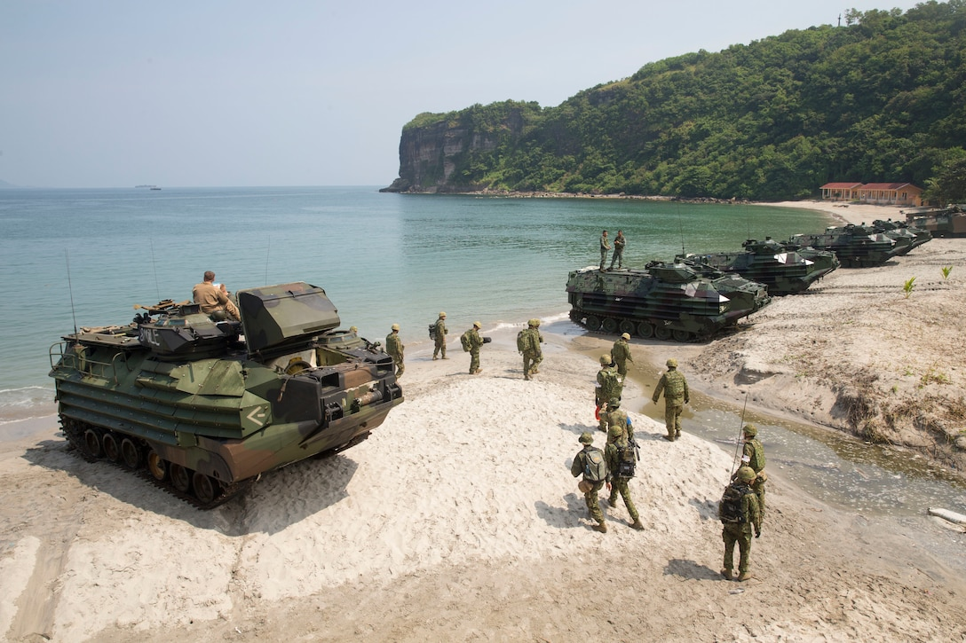 """U.S. Marine, Philippine Marine and Japan Ground Self-Defense Force members assault amphibious vehicles line up along the shore following an amphibious exercise as part of KAMANDAG 3 at Katungkulan Beach, Marine Barracks Gregorio Lim, Philippines, Oct. 12, 2019. KAMANDAG helps participating forces maintain a high level of readiness and responsiveness, and enhances combined military-to-military relations, interoperability, and multinational coordination. KAMANDAG is an acronym for the Filipino phrase """"Kaagapay Ng Mga Manirigma Ng Dagat,"""" which translates to """"Cooperation of the Warriors of the Sea,"""" highlighting the partnership between the U.S. and Philippine militaries."""