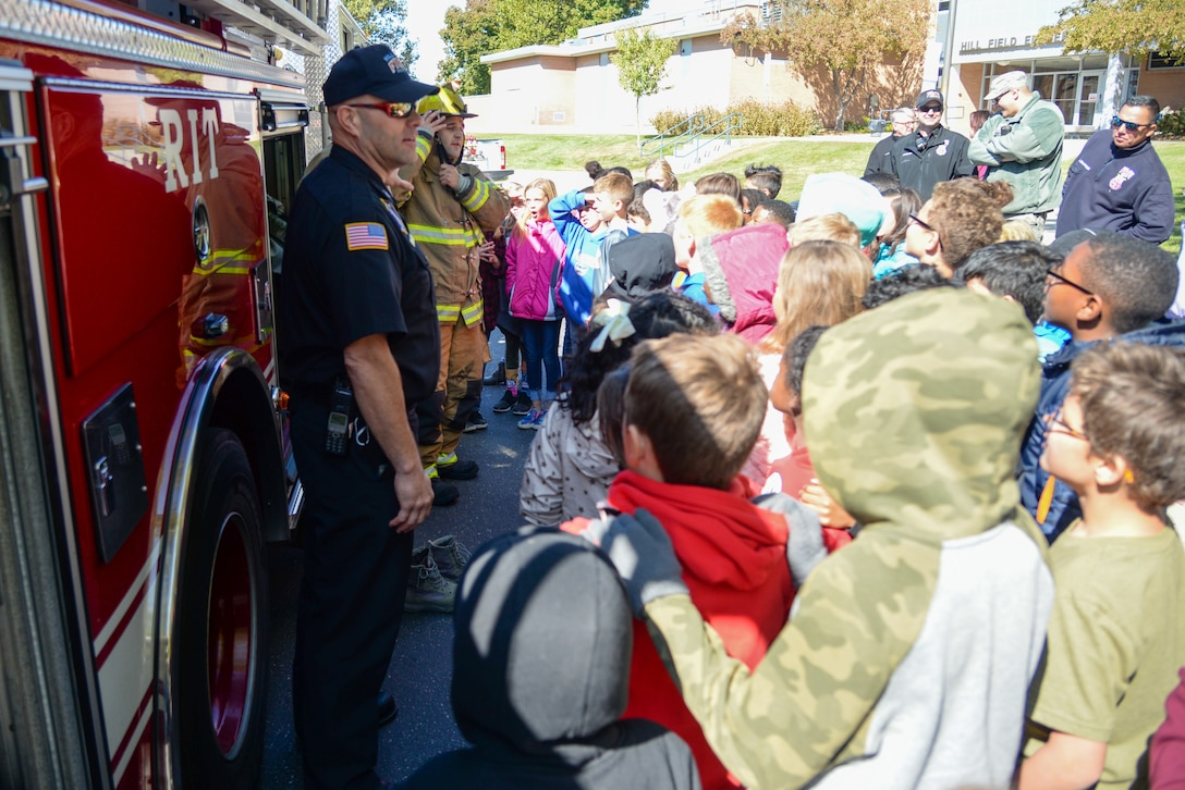 (Left to right) Doran Smith and Airman 1st Class Gabriel Briones, Fire and Emergency Services at Hill Air Force Base, Utah, demonstrate firefighting equipment for Hill Field Elementary students Oct. 10, 2019, in front of the department's fire engine. This was one of the numerous outreach events base firefighters sponsored for Fire Prevention Week Oct. 6-12. (U.S. Air Force photo by Cynthia Griggs)