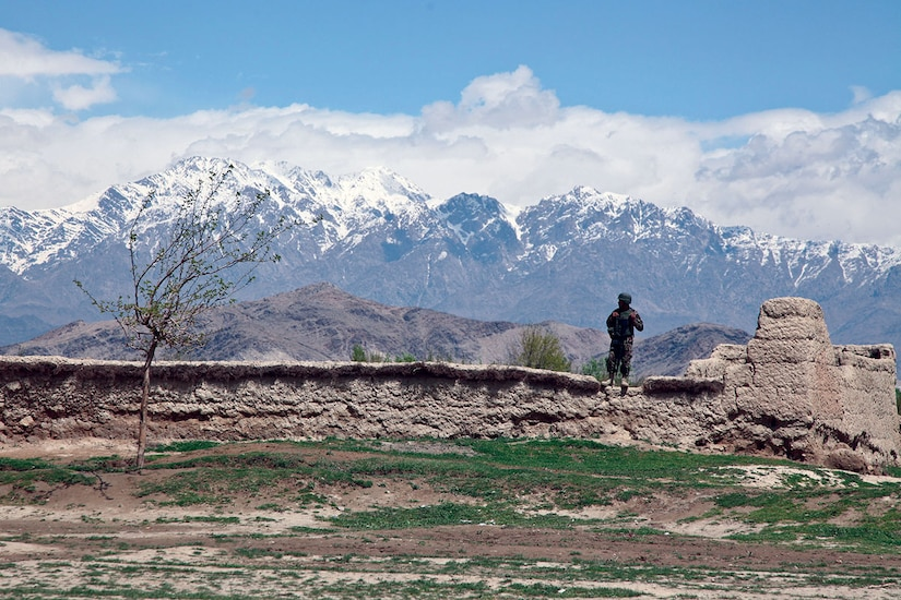 In 2014, an Afghan military police officer stands on a wall while providing security in a village near Bagram airfield. (U.S. Army/Nikayla Shodeen)