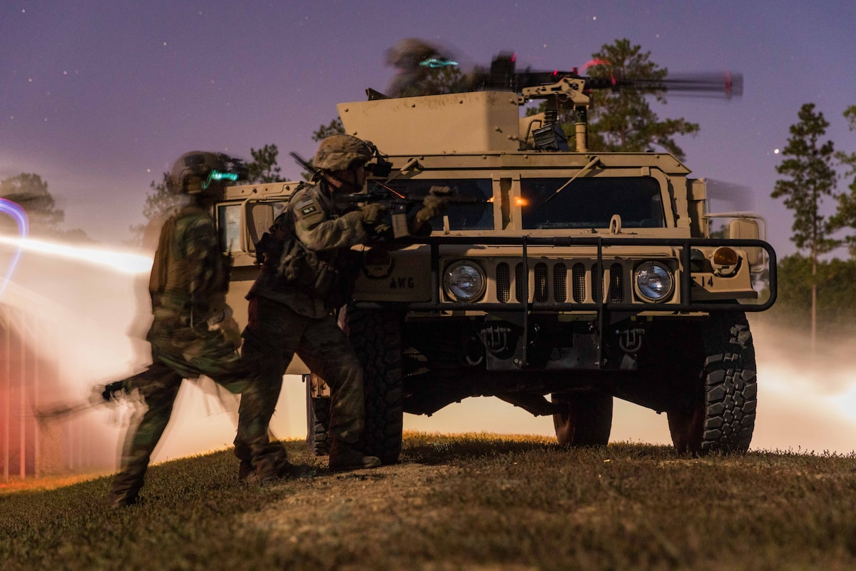 Soldiers stand around a military vehicle pointing their weapons toward a simulated target.